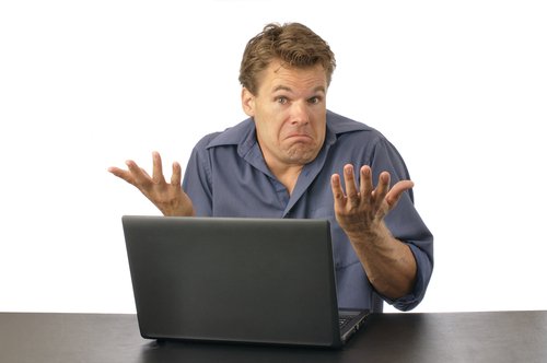 Man at laptop shrugging