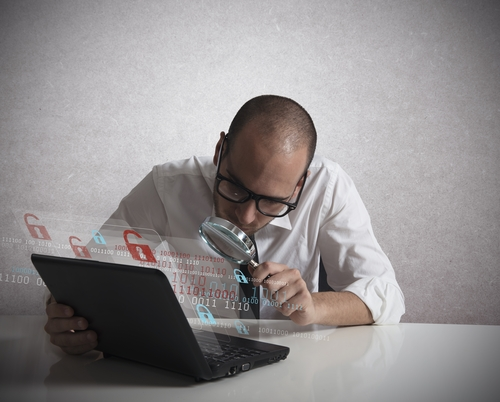 Man with magnifying glass and laptop